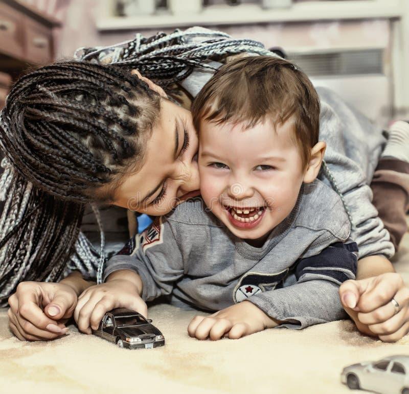 Juegos de piel morena de la madre con su hijo La mamá latinoamericana juega y ríe con su pequeño hijo Concepto: Día feliz del ` s fotos de archivo libres de regalías
