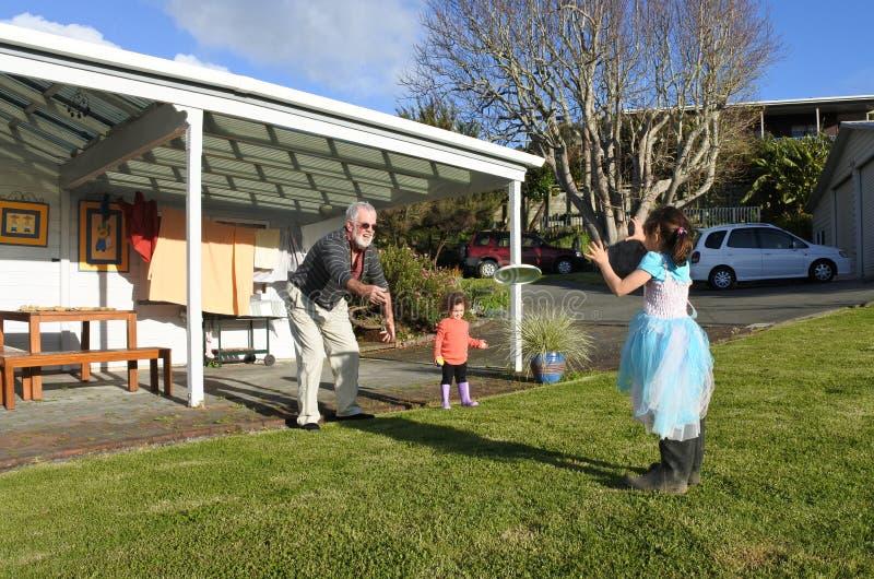 Juegos del abuelo con sus hijas al aire libre fotografía de archivo