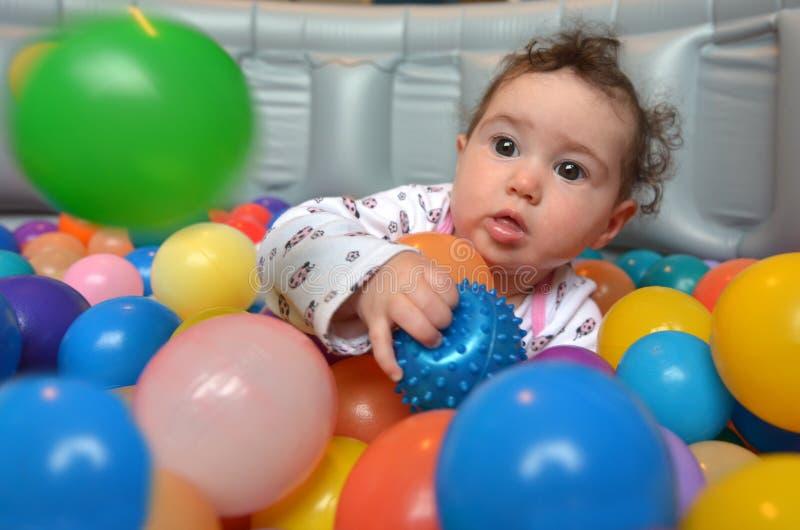 Juegos del bebé con las bolas coloridas fotos de archivo