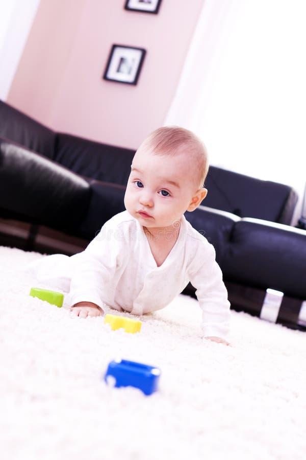Juegos del bebé en la sala de estar moderna. foto de archivo