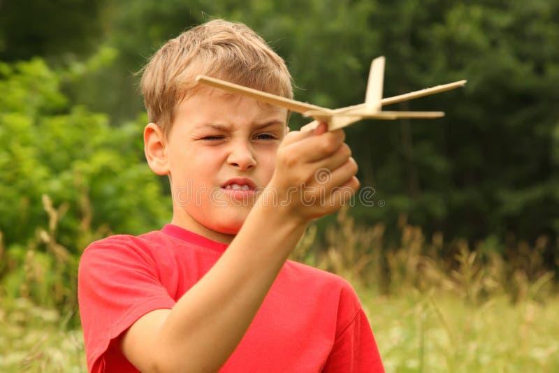 Juegos del muchacho con el aeroplano de madera en la naturaleza fotos de archivo