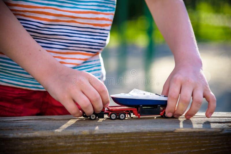 Juegos del muchacho con los coches del juguete Ni?o que juega en el patio solamente La diversi?n diurna del ni?o foto de archivo