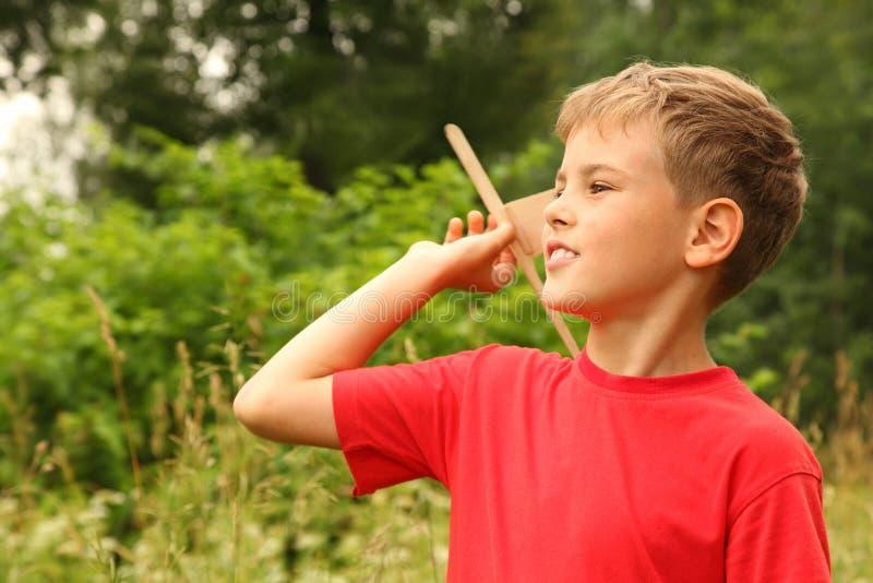 Juegos del niño pequeño con el aeroplano de madera en la naturaleza fotografía de archivo libre de regalías