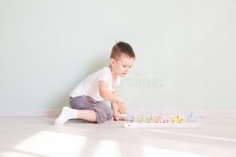 Juegos del niño pequeño con el coche del juguete en casa fotografía de archivo libre de regalías
