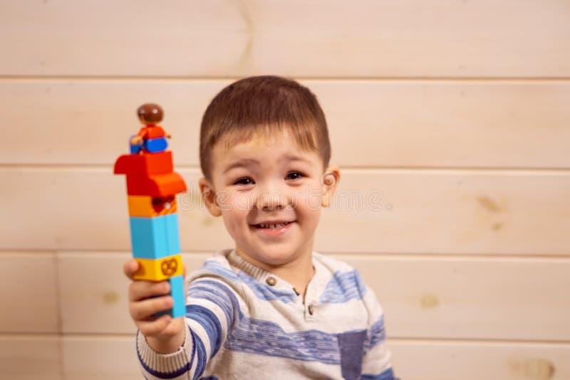 Juegos del niño pequeño con el coche del juguete en casa imagenes de archivo