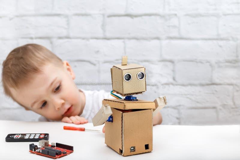 Juegos del niño pequeño con el robot en casa Robot de exploración del niño foto de archivo