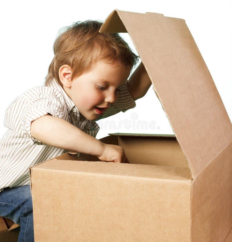 Juegos del niño pequeño en cajas foto de archivo libre de regalías