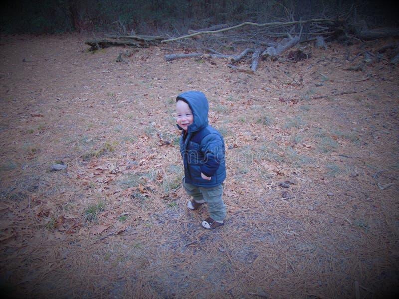 Juegos del niño pequeño en el bosque imagenes de archivo