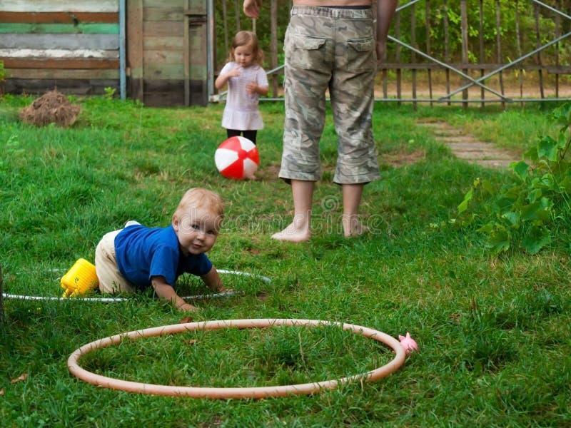 Juegos del padre con los niños en diversos juegos fotos de archivo