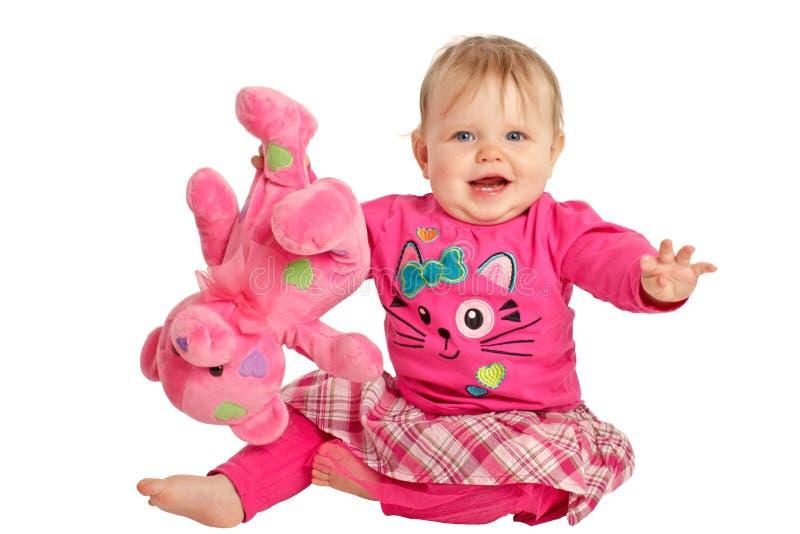 Juegos felices de la niña con el oso de peluche rosado fotografía de archivo