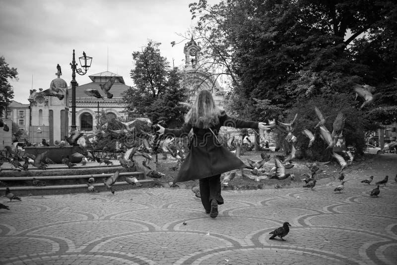 Juegos hermosos de la muchacha del otoño con las palomas en Sofía fotos de archivo