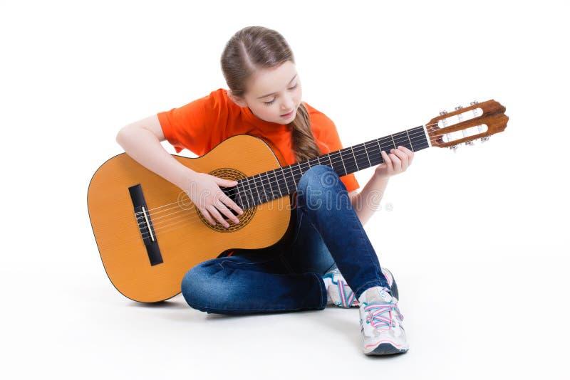 Juegos lindos de la muchacha en la guitarra acústica. imagen de archivo