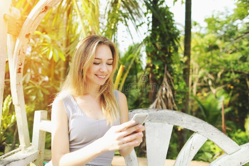 Juegos rubios del juego de la mujer en el smartphone, fondo del día soleado de palmas del verde de la sol en viaje de Tailandia,  imagenes de archivo