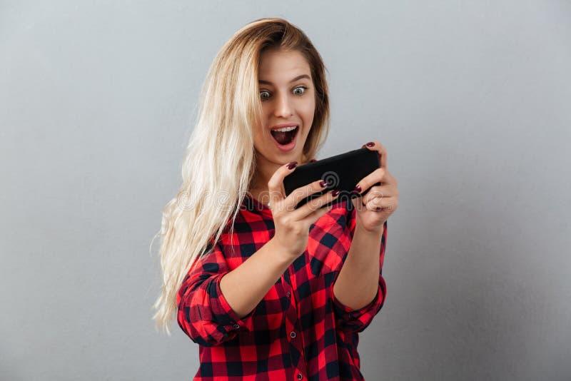 Juegos rubios jovenes asombrosos del juego de la mujer por el teléfono fotos de archivo