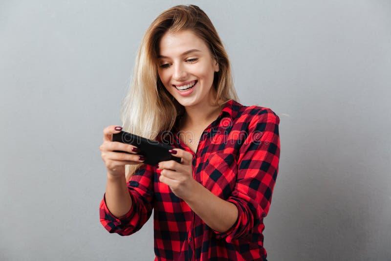 Juegos rubios jovenes asombrosos del juego de la mujer por el teléfono foto de archivo