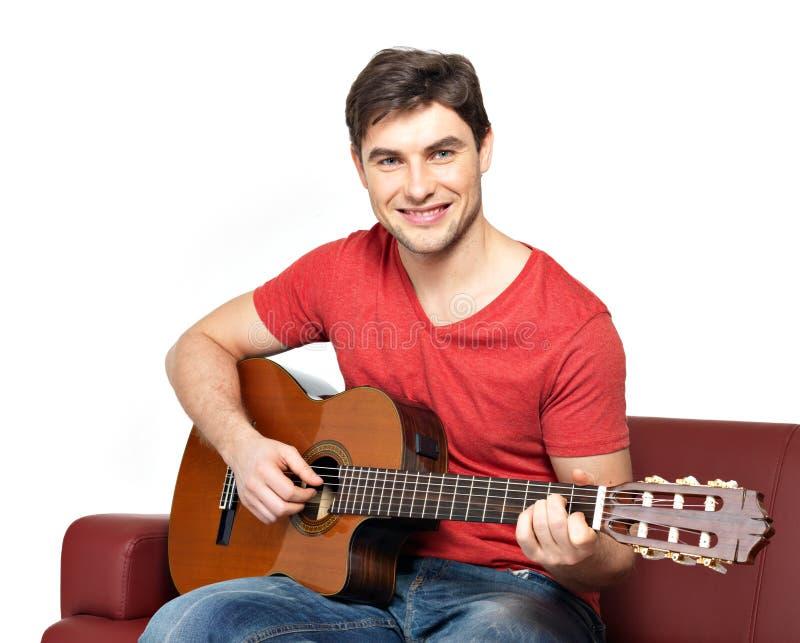 Juegos sonrientes del guitarrista en el guitat acústico fotografía de archivo