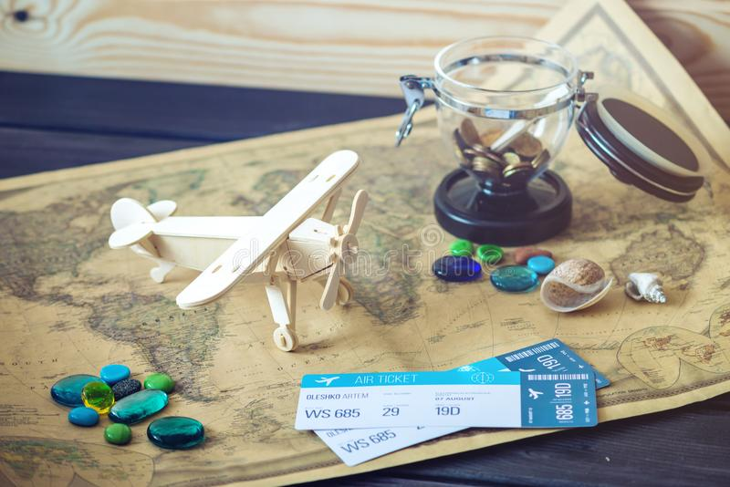 Juegue el avión de madera en un mapa del mundo con las piedras y las cáscaras coloreadas del mar en un estilo retro imágenes de archivo libres de regalías
