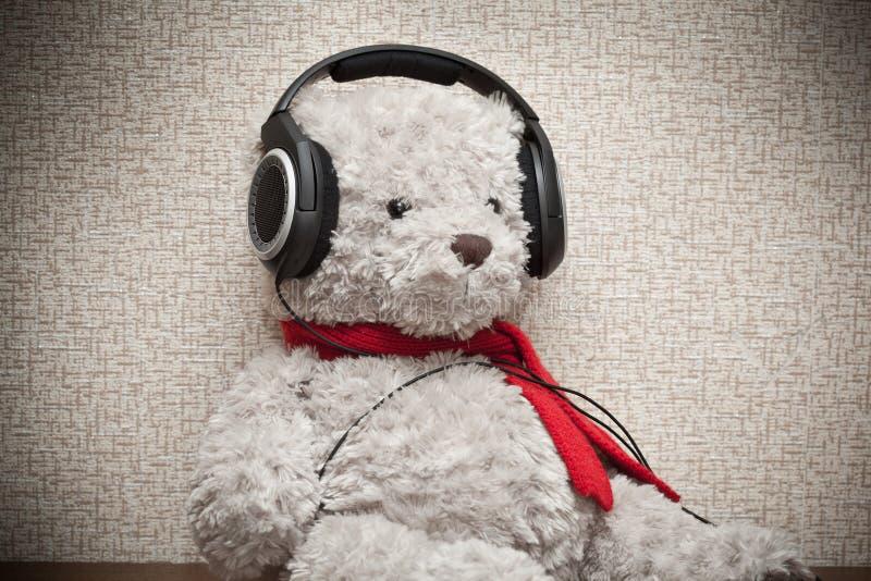 Juegue el oso de peluche con una bufanda roja que escucha la música en los auriculares fotografía de archivo