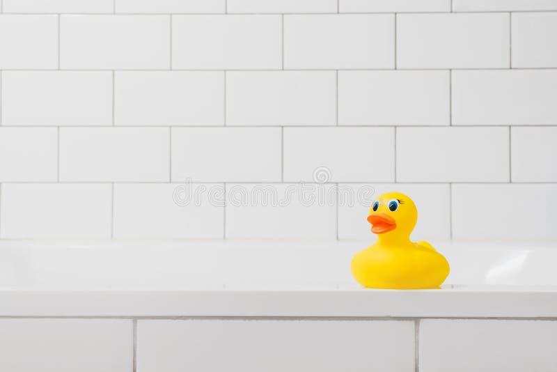 Juegue el pato amarillo en el cuarto de baño en un fondo ligero del ladrillo foto de archivo libre de regalías