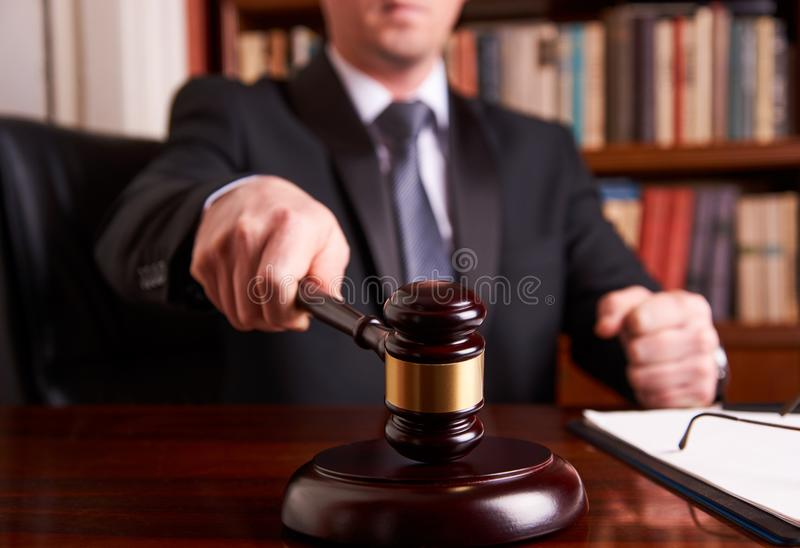 Juez masculino In una sala de tribunal que pega el mazo fotos de archivo