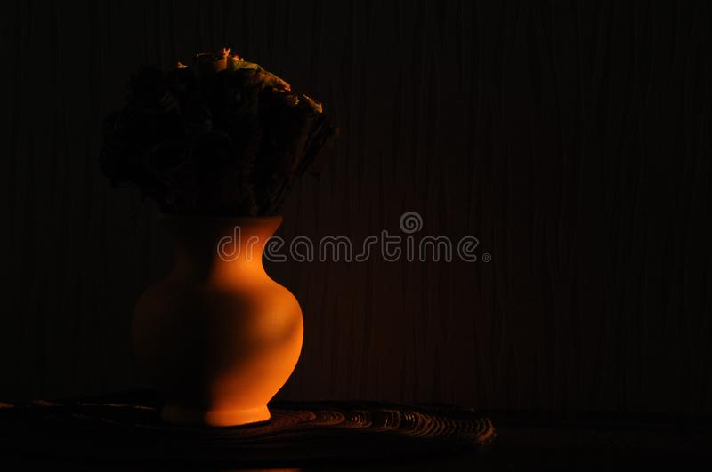 Jug with a bouquet of dried leaves resembling roses, lit the rising sun stock photography