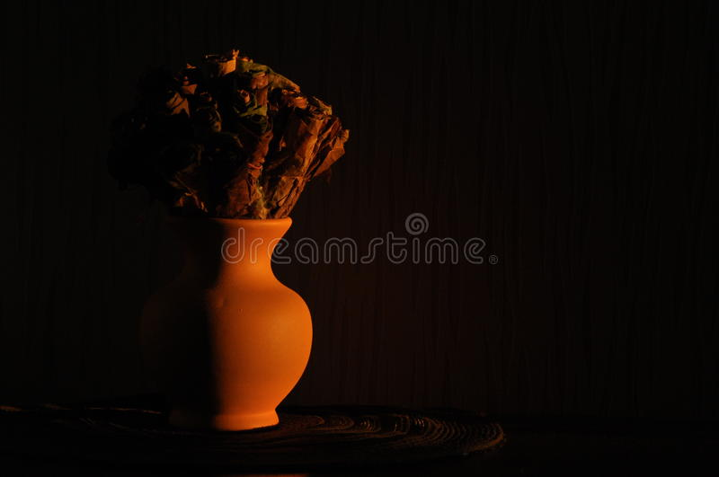 Jug with a bouquet of dried leaves resembling roses, lit rising sun. Jug with a bouquet of dried leaves resembling roses, lit the rising sun royalty free stock photos