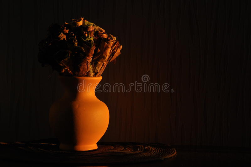 Jug with a bouquet of dried leaves resembling roses, lit the rising stock image