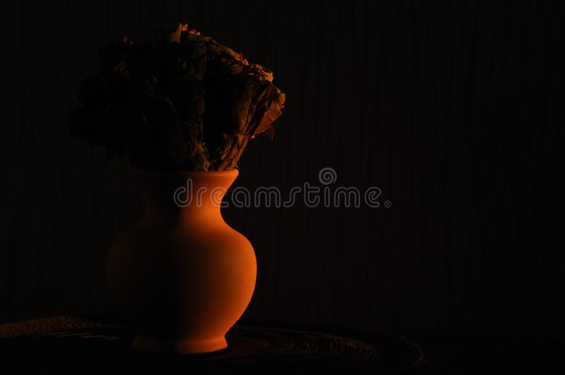 Jug with a bouquet of dried leaves resembling roses royalty free stock photos
