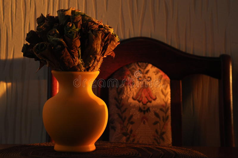 Jug with a bouquet of dried leaves resembling roses royalty free stock image