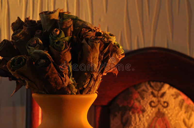Jug with a bouquet of dried leaves resembling roses stock images