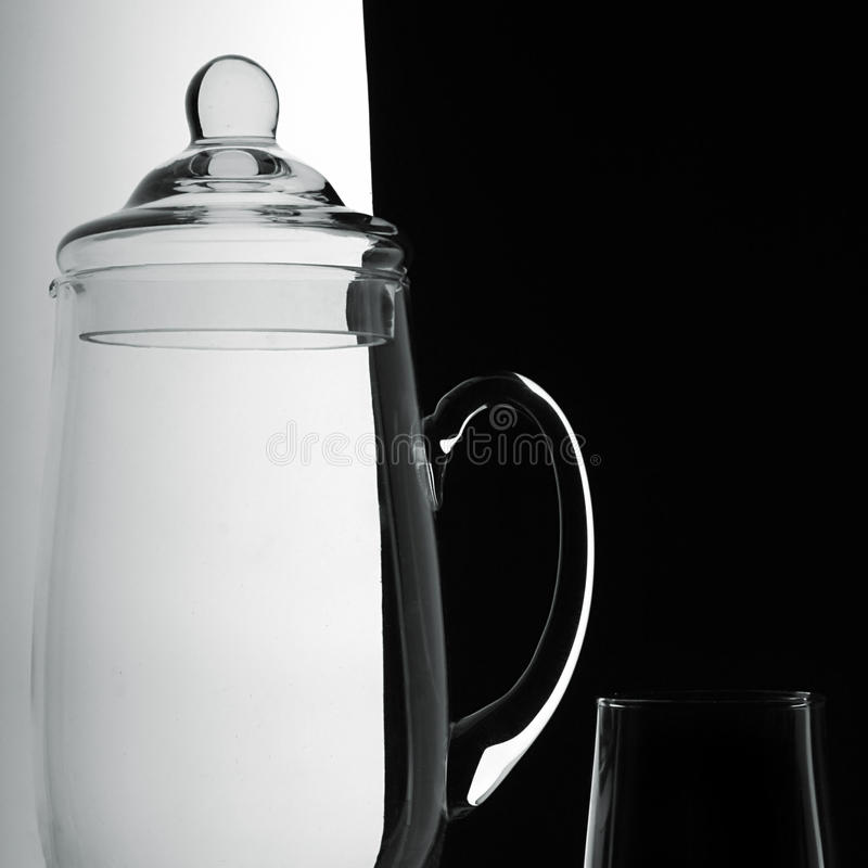 Jug and glass on a black-and-white background royalty free stock images