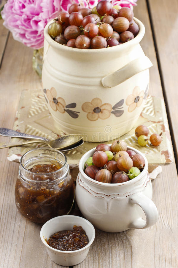 Jug of gooseberries on wooden table. Summer fruits stock photos