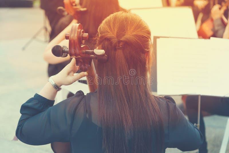 Jugador asiático del violoncelo de la mujer en un concierto al aire libre libre en un público p fotos de archivo