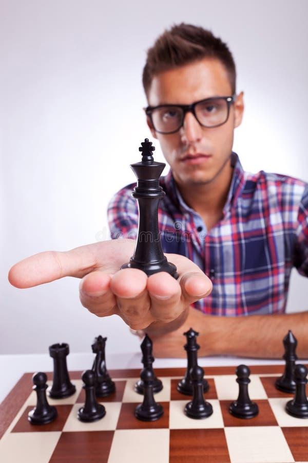 Jugador de ajedrez del hombre joven que soporta a su rey foto de archivo