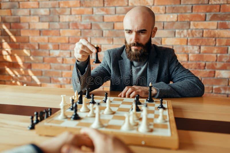 Jugador de ajedrez que juega las figuras negras, movimiento de la reina fotos de archivo libres de regalías