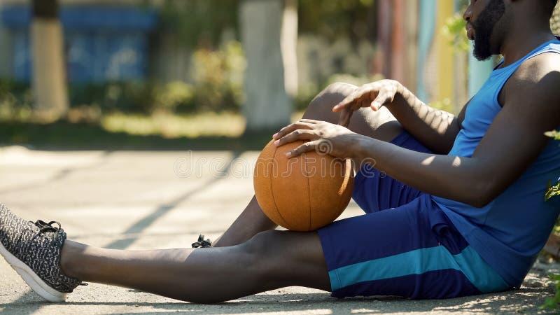 Jugador de básquet afroamericano solo que se sienta en la tierra con la bola, tristeza fotografía de archivo