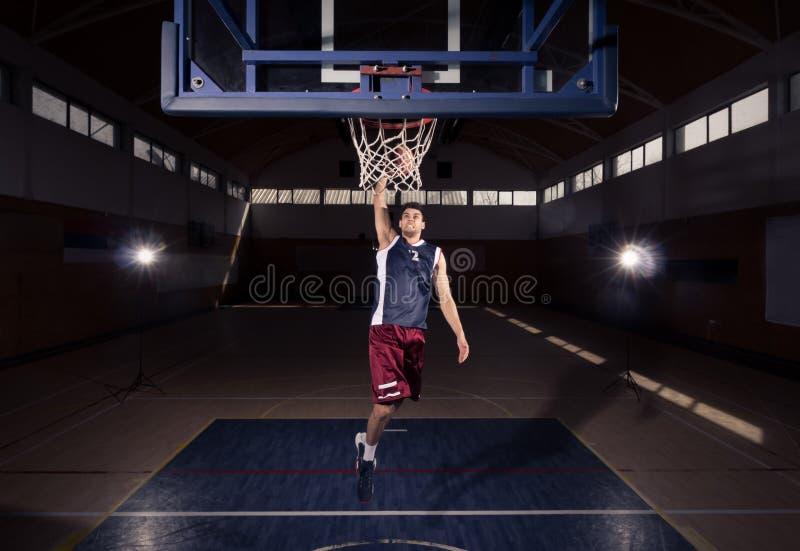 Jugador de básquet, clavada en el aire, dentro cou oscuro del baloncesto foto de archivo libre de regalías