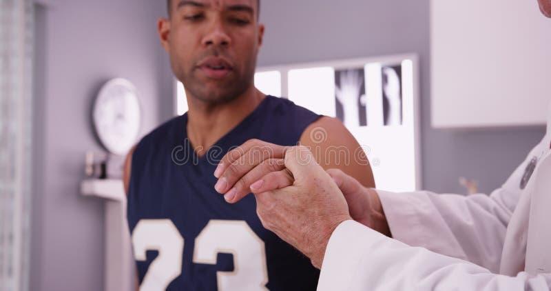 Jugador de básquet de la universidad con lesión de los deportes que es examinada por d fotos de archivo