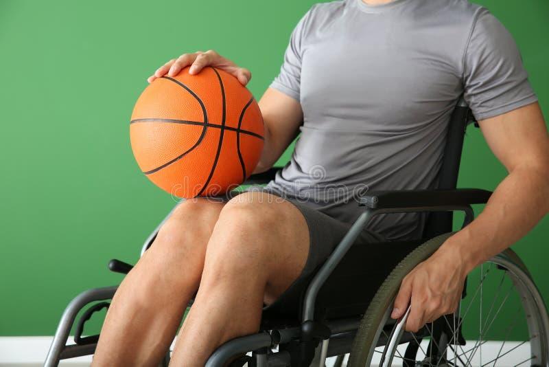 Jugador de básquet joven que se sienta en silla de ruedas contra la pared del color imagen de archivo libre de regalías