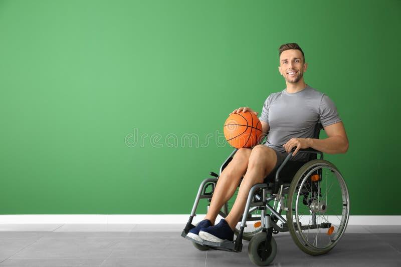 Jugador de básquet joven que se sienta en silla de ruedas contra la pared del color foto de archivo libre de regalías