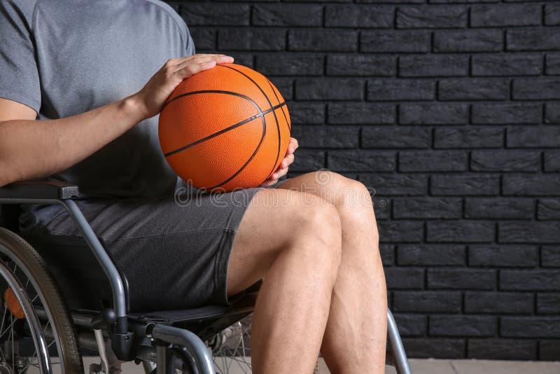 Jugador de básquet joven que se sienta en silla de ruedas contra la pared de ladrillo oscura fotografía de archivo libre de regalías