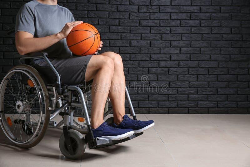 Jugador de básquet joven que se sienta en silla de ruedas contra la pared de ladrillo oscura fotografía de archivo