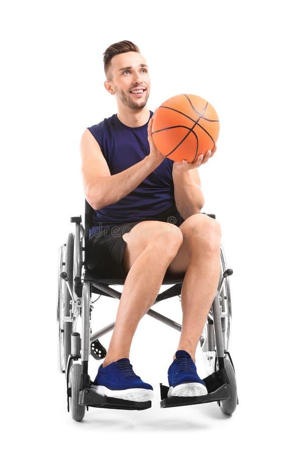 Jugador de básquet joven que se sienta en silla de ruedas en el fondo blanco fotografía de archivo