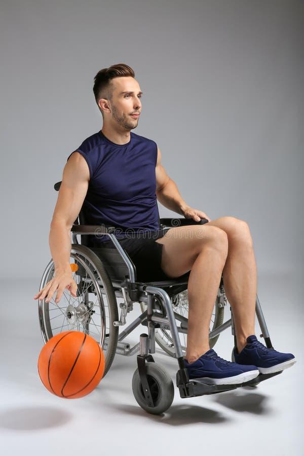 Jugador de básquet joven que se sienta en silla de ruedas en fondo gris fotos de archivo
