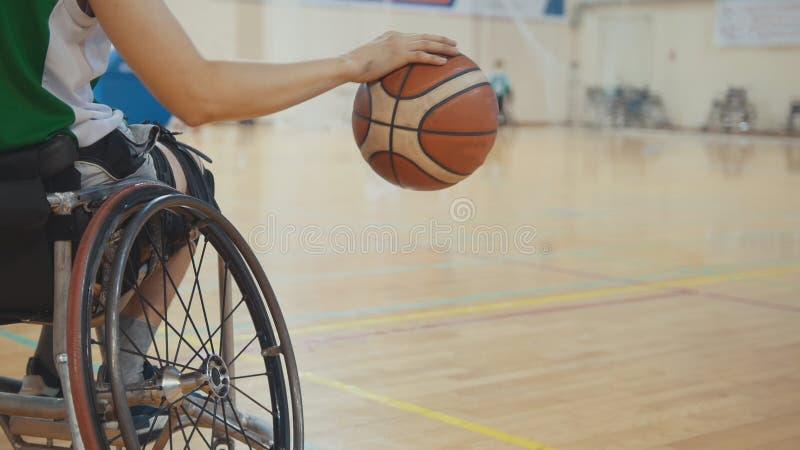 Jugador de básquet de la silla de ruedas que gotea la bola rápidamente durante el entrenamiento de deportistas discapacitados fotos de archivo