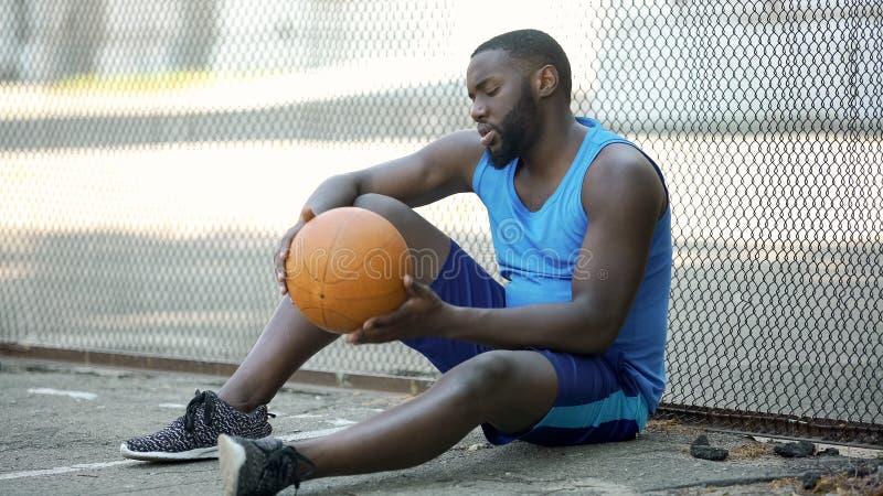 Jugador de básquet negro solo que se sienta en la tierra del estadio y que celebra la bola, deporte foto de archivo
