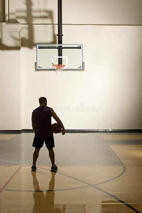 Jugador de básquet solamente en cancha de básquet imagen de archivo libre de regalías