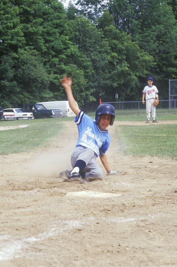 Jugador de béisbol que resbala dentro de la base, juego de la liga pequeña, Hebrón, CT fotos de archivo