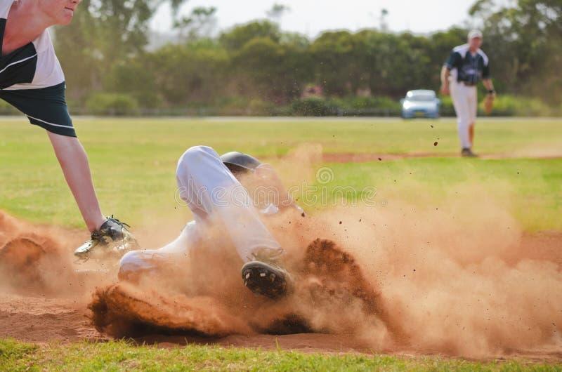 Jugador de béisbol que resbala dentro de la tercera base imagenes de archivo