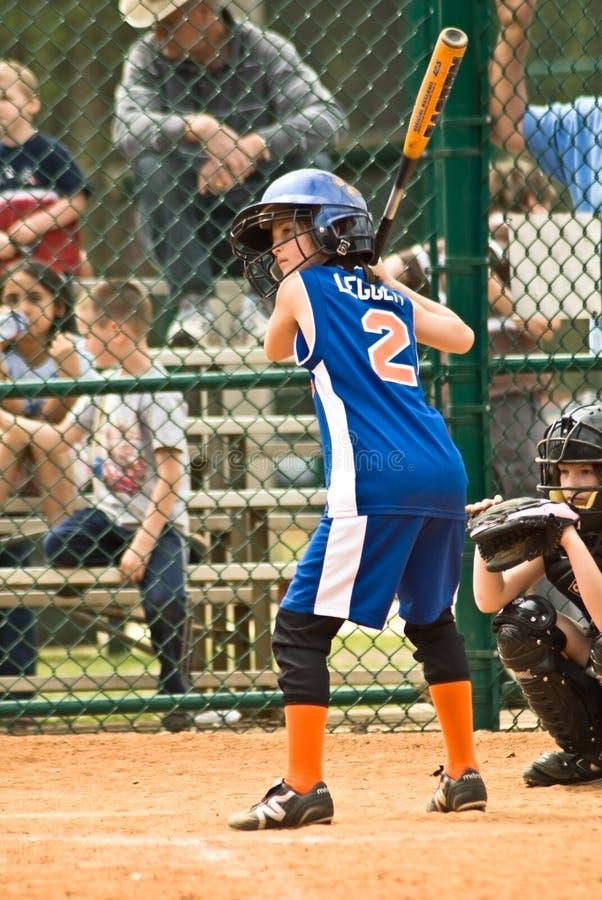 Jugador de beísbol con pelota blanda de la chica joven imagen de archivo